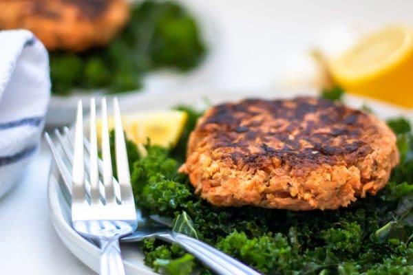 A salmon patty on a massaged kale salad with lemons on the side.