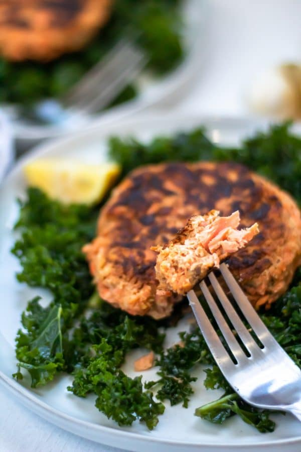 A forkful of salmon patty from a salmon patty on a bed of massaged kale with a lemon wedge on the side.