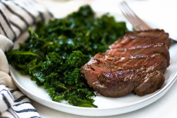 Horizontal image of sliced cast iron skillet steak next to massaged kale salad.