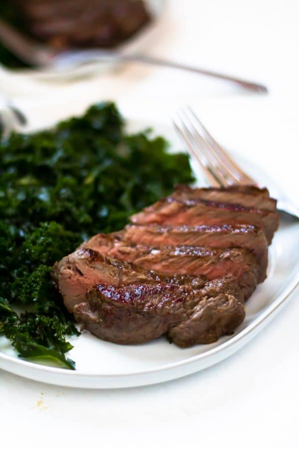 A seared and sliced cast iron skillet steak on a white plate with massaged kale salad.