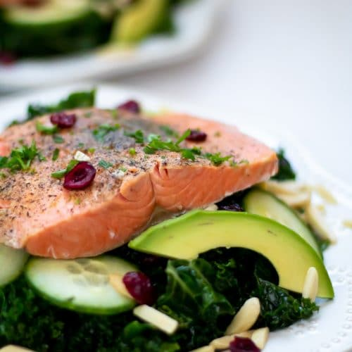Instant Pot Salmon over a massaged kale salad with avocado, cucumbers, dried cranberries, and almond slivers.