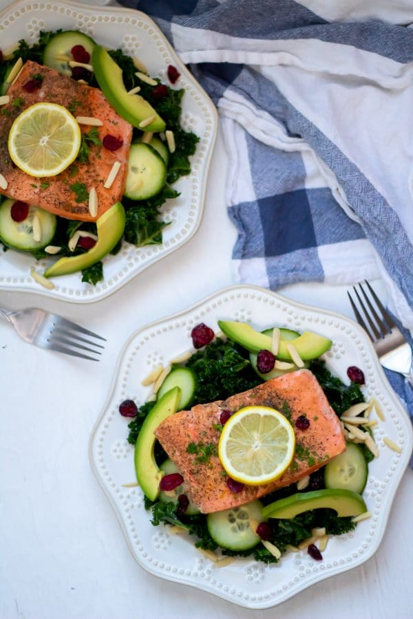 Overhead shot of two kale salads topped with salmon and lemon wedges with a white and blue dish towel to the side on a white wooden board.