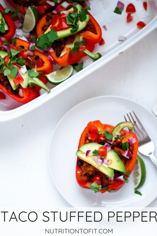 A taco stuffed red bell pepper on a white plate with white background topped with fresh avocado, tomato, cilantro, lime, and red onion.