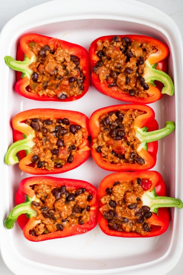 Red bell peppers stuffed with turkey filling for taco stuffed peppers in a white casserole dish.