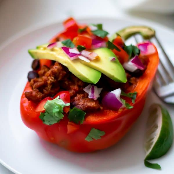 A close up of a taco stuffed pepper with fresh taco toppings like avocado, red onion, and cilantro.