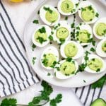 Cream ceramic plate with avocado deviled eggs garnished with cilantro on a black and cream striped linen towel and lemons, avocado, and cilantro surrounding it.