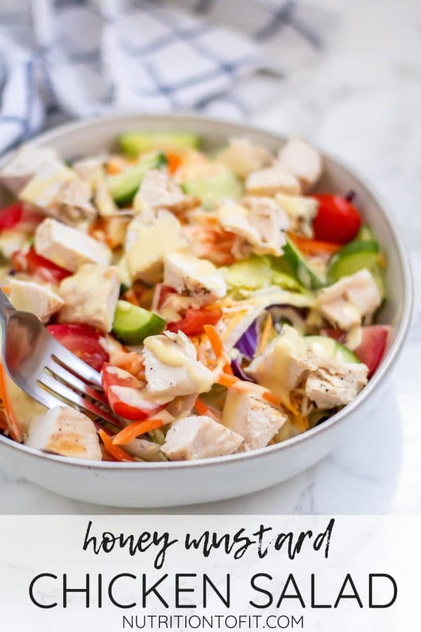 """Pinterest image of A fork in a bowl of honey mustard chicken salad with text that says """"honey mustard chicken salad nutritiontofit.com"""""""