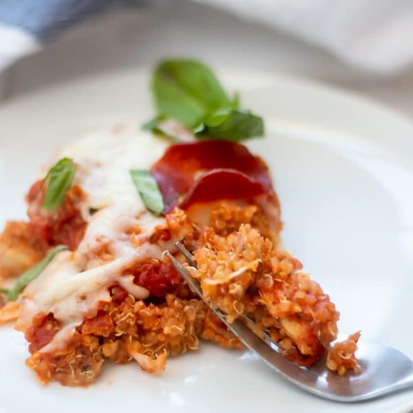 A bite of pizza quinoa casserole showing chicken inside casserole.