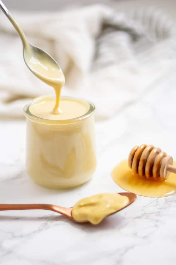 A spoon drizzling healthy honey mustard dressing back into a glass jar of dressing.