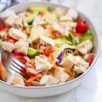 A fork in a bowl of honey mustard chicken salad.