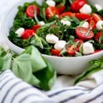 Kale caprese salad in a cream ceramic shallow owl surrounded by fresh basil and tomatoes.