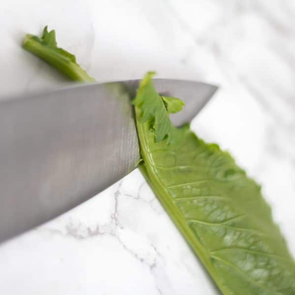 a knife slicing the turnip green leaves off the stem
