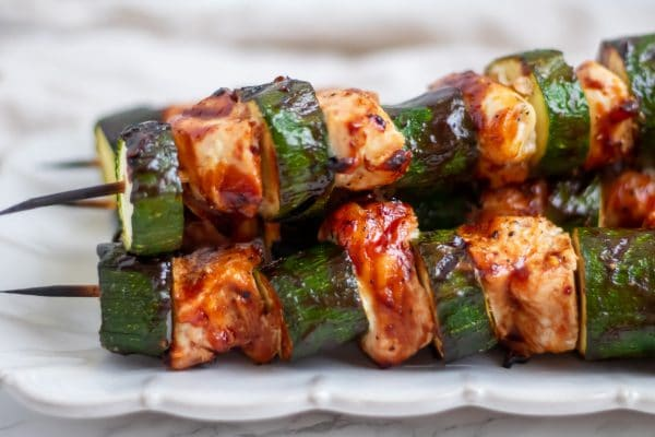 side shot of bbq chicken skewers with alternating chicken and zucchini