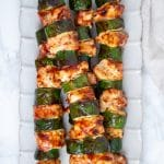 BBQ chicken skewers with zucchini on an ivory plate.