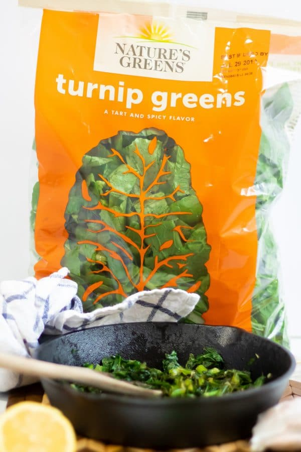 A bright orange bag of pre-washed and pre-chopped Nature's Greens turnip greens behind a small cast iron skillet with sauteed lemon garlic turnip greens and a wooden spoon.