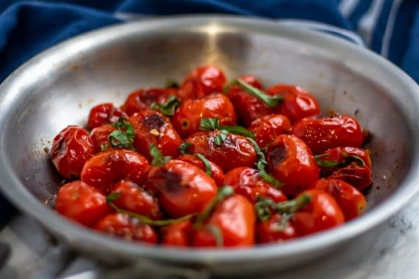 blistered tomatoes in a pan, garnished with fresh basil
