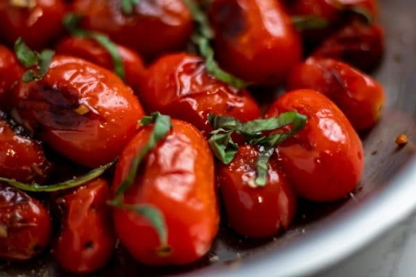 close up of blistered tomatoes with fresh basil