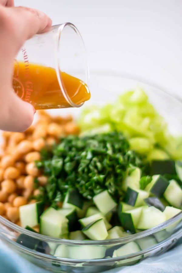 Pouring a simple red wine vinaigrette over the ingredients for cucumber chickpea salad.