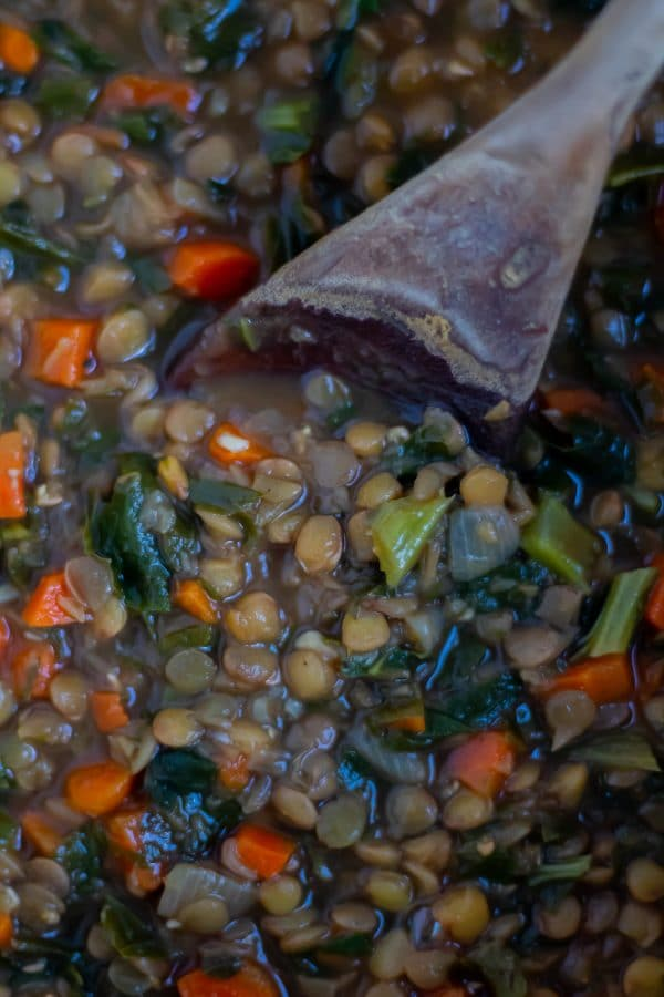 Close up of a wooden spoon in lentil stew specked witht turnip greens and carrots