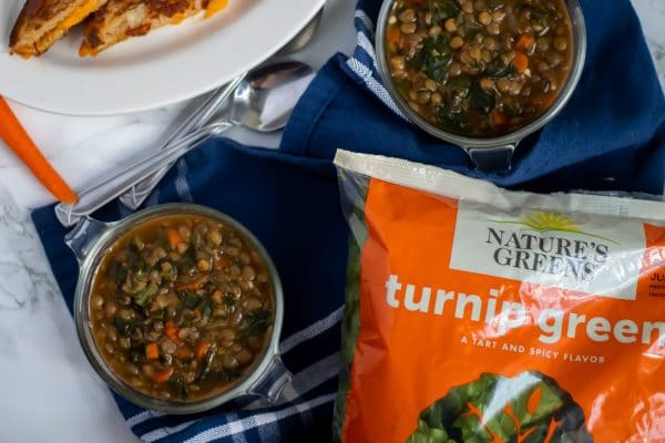 Two antique glass bowls of lentil stew on a blue towel with a bag of Nature's Greens turnip greens, featured in the stew