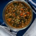 An overhead of a glass bowl filled with lentil stew with turnip greens