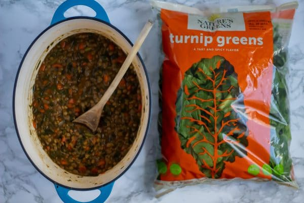 A blue oval dutch oven of lentil stew next to an orange bag of Nature's Green turnip greens
