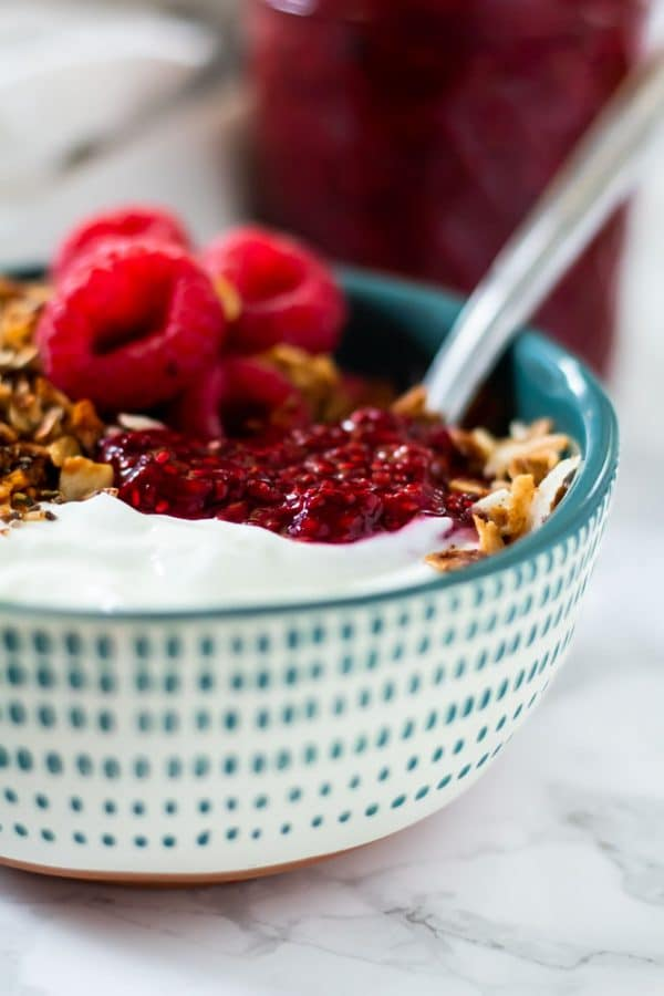 yogurt parfait with raspberries, granola, and raspberry chia jam in a white and teal spotted rustic bowl.