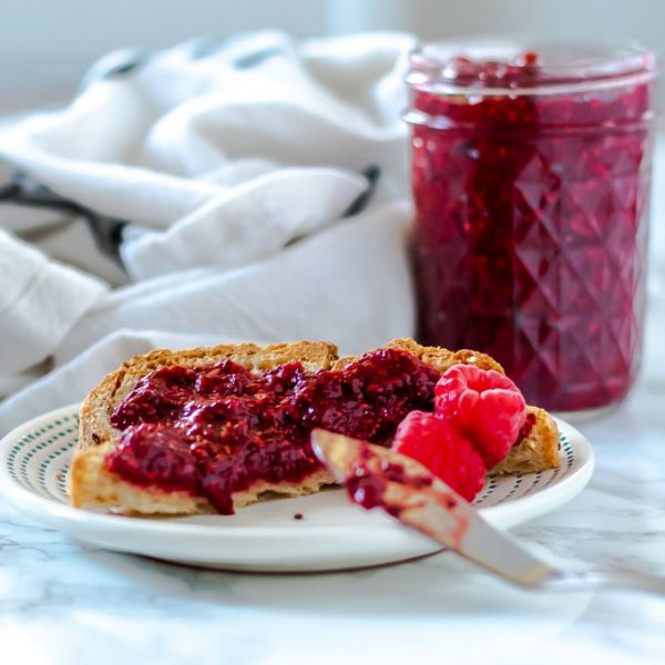 toast with raspberry jam with a mason jar of jam in the background