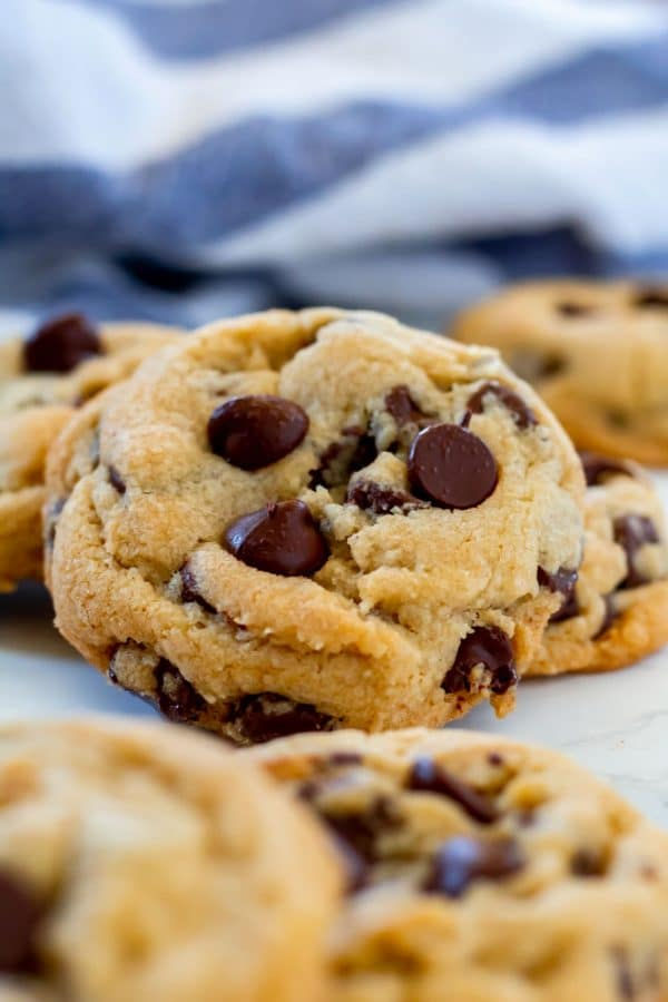 a gluten-free chocolate chip cookie propped against other cookies