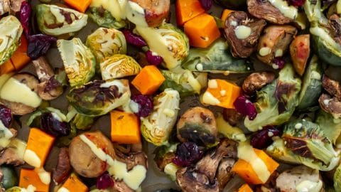 roasted butternut squash, brussels sprouts, mushrooms, chicken sausage with dried cranberries and a honey mustard drizzle on a sheet pan