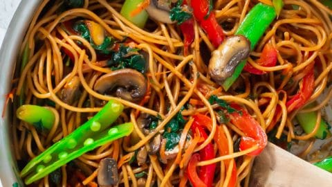 Steel pan of lo mein with bright vegetables and a wooden spoon.