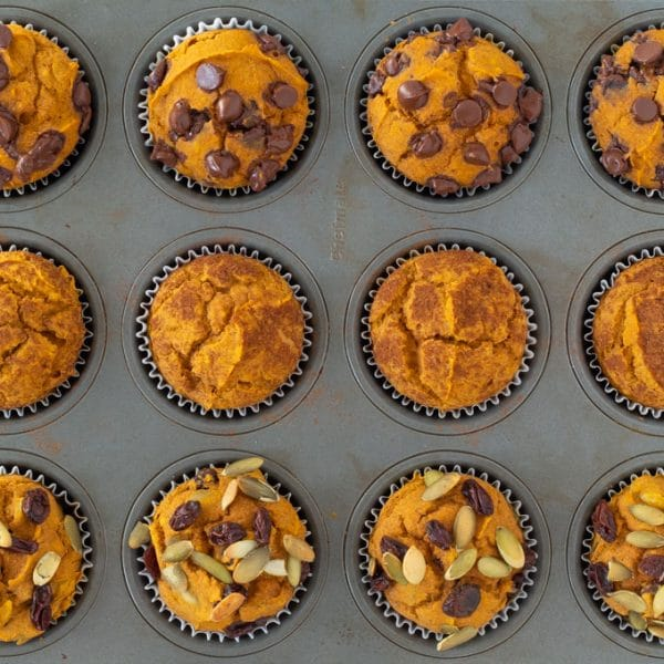 pumpkin muffins in a silver pan - the top row with chocolate chips, the middle row with cinnamon, and the bottom row with raisins and pumpkin seeds.