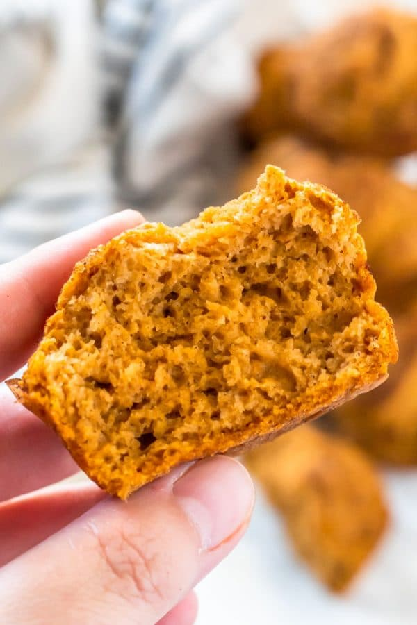 Holding half a pumpkin muffin to show the light, fluffy texture of this easy, gluten free muffin.