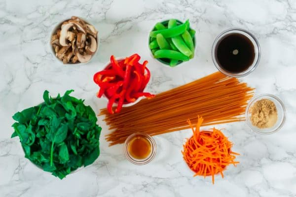 assembled ingredients (spinach, mushrooms, bell pepper, lentil pasta, carrots, sugar snap peas, coconut aminos, brown sugar, and spices) required to make easy, gluten-free lo mein