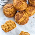 a pile of pumpkin muffins with one broken in half, facing up