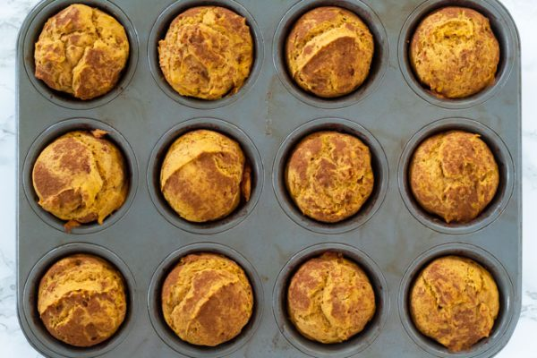 pumpkin muffins in a metal pan with cinnamon sprinkled on top
