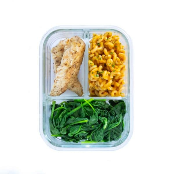 A 3-compartment glass meal prep container featuring pumpkin pasta, grilled chicken tenderloins, and steamed spinach.