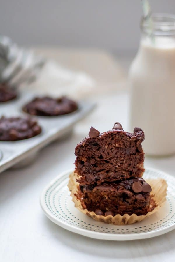 a double chocolate banana muffin cut in half, with the halves stacked on each other and the pan of muffins and bottle of milk in the background.