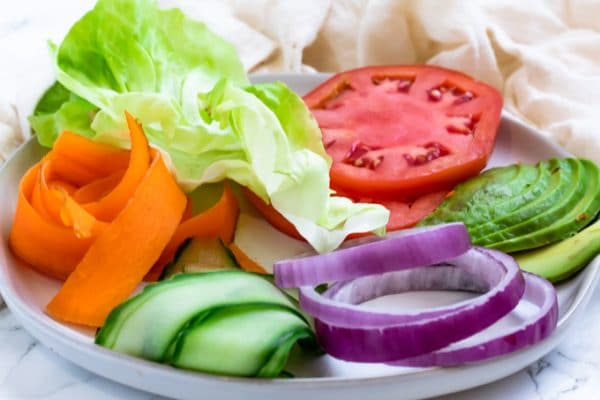 a plate of vegetable toppings for a sandwich (carrot, lettuce, tomato, avocado, red onion, cucumber)