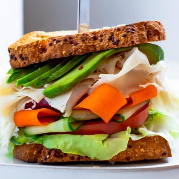 straight on shot of a whole grain sandwich with turkey, avocado, veggies, and hummus