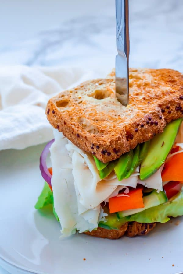 sandwich with deli turkey, avocado, lots of veggies on whole grain bread on a white plate with a butter knife in it.