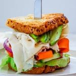 turkey avocado sandwich on whole grain bread loaded with veggies on a white ceramic plate