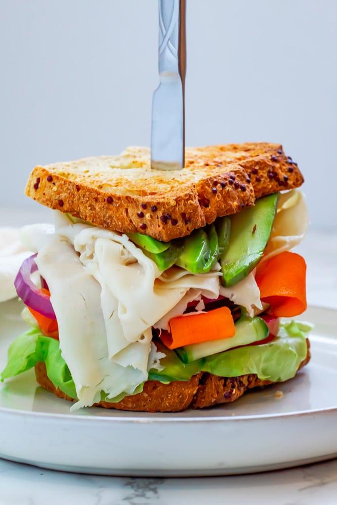 turkey avocado sandwich on whole grain bread loaded with veggies on a white ceramic plate
