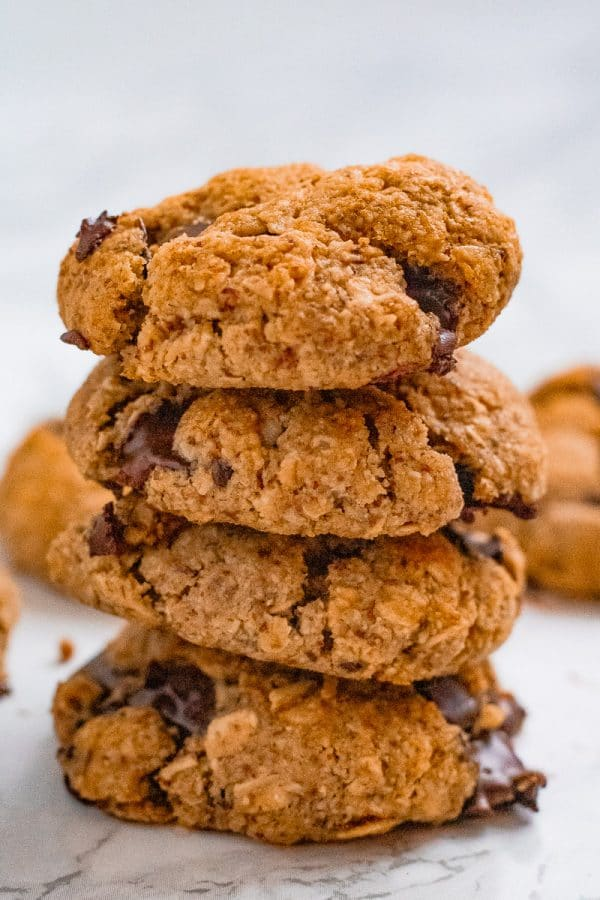 a brightly lit stack of 4 almond oat cookies with chocolate chips on marble