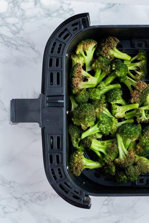 crispy air fried broccoli in a black air fryer basket