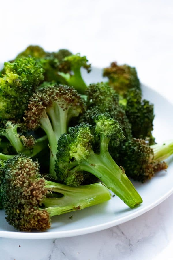 crispy broccoli florets on a white plate