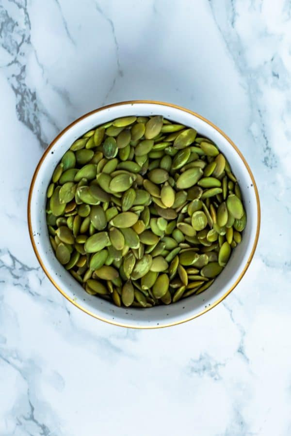 Pumpkin seeds in a white bowl on a marble surface.