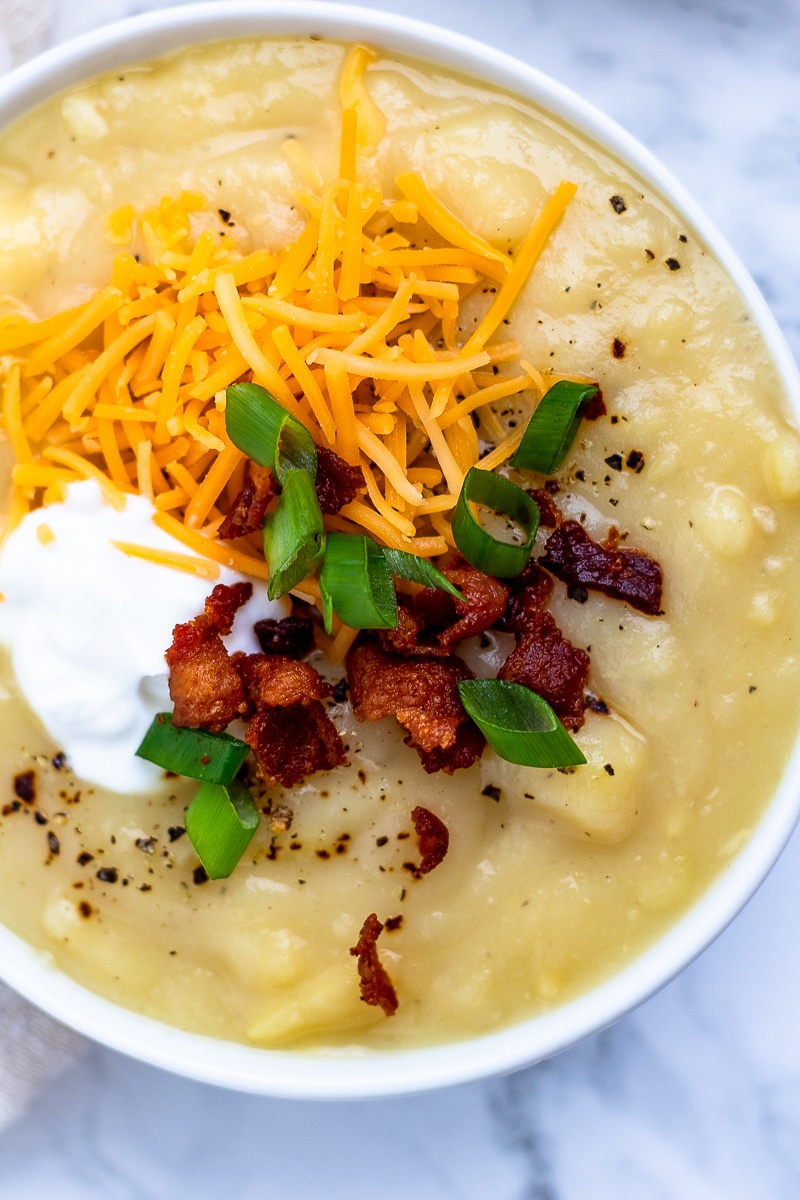 A close up of a white bowl of potato soup topped with bacon, cheese, greek yogurt and green onions.