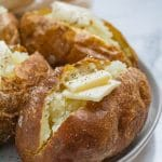 baked potatoes with butter on a ceramic plate