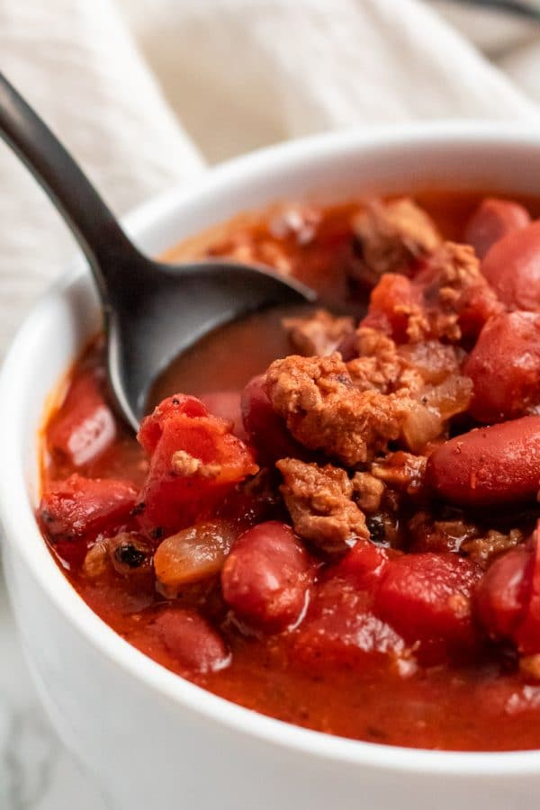 A black spoon in a white bowl of gluten-free turkey chili